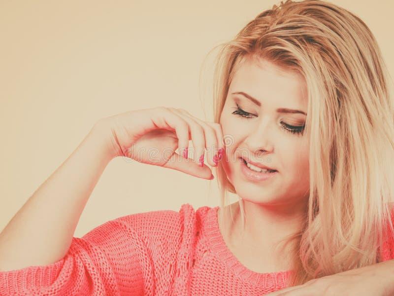 Atrakcyjna blondynki kobieta patrzeje w dół i myśleć obraz royalty free