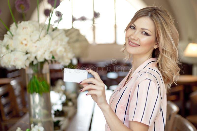 Atrakcyjna blondynki kobieta trzyma biel pustą pustą wizytówkę zdjęcia stock