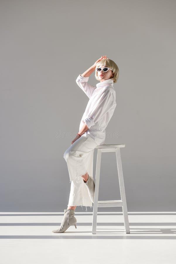 atrakcyjna blondynki kobieta w okularach przeciwsłonecznych, modnym białym stroju obsiadaniu i pozować na krześle fotografia royalty free