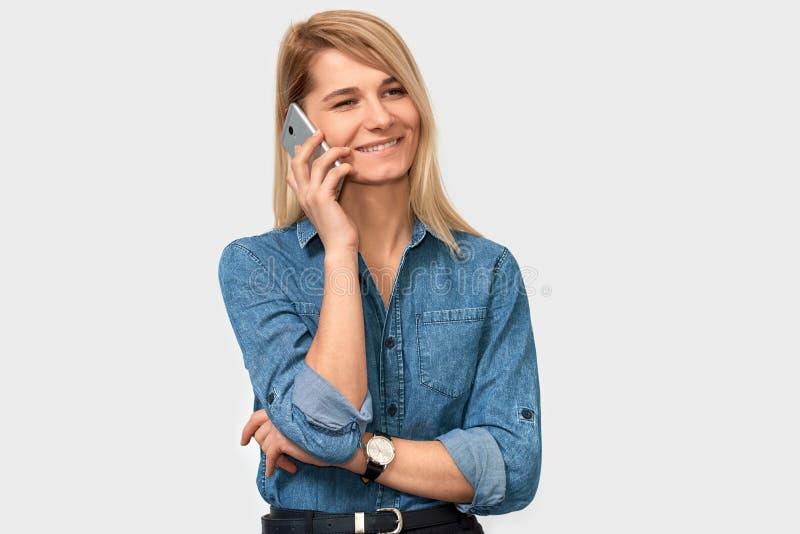 Atrakcyjna blondynki młoda kobieta opowiada na telefonie komórkowym jej przyjaciel, patrzejący rozochocony i szczęśliwy, pozujący fotografia royalty free