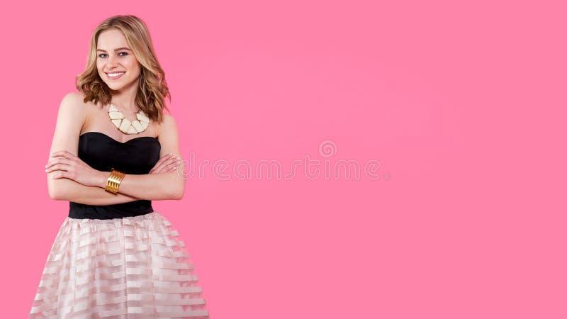 Atrakcyjna blondynki młoda kobieta w eleganckiej partyjnej sukni i złotej biżuterii Dziewczyna pozuje na pastelowych menchii tle fotografia royalty free