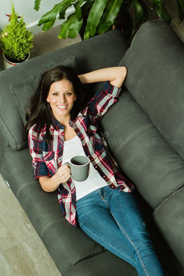 Atrakcyjna brunetki dziewczyna odpoczywa na kanapie obrazy royalty free