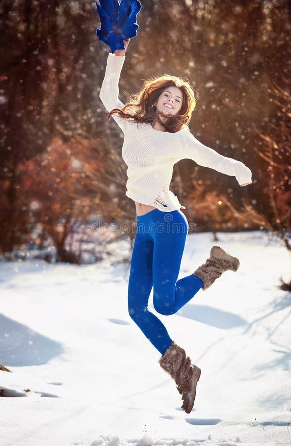 Atrakcyjna brunetki dziewczyna z białym pulowerem pozuje bawić się w zimy scenerii. Piękna młoda kobieta z długie włosy cieszy się zdjęcie stock