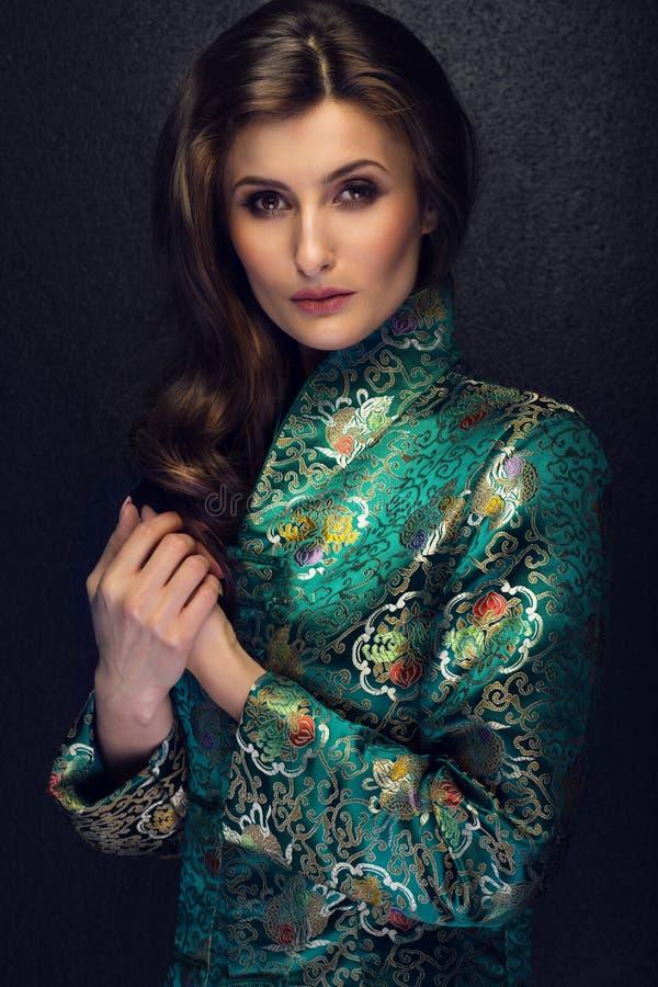 Atrakcyjna brunetki kobieta pozuje w modnym Japońskim stylu j fotografia royalty free