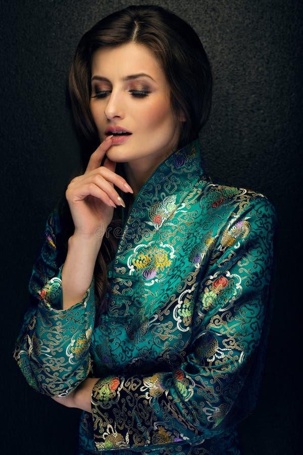 Atrakcyjna brunetki kobieta pozuje w modnym Japońskim stylu j zdjęcia royalty free