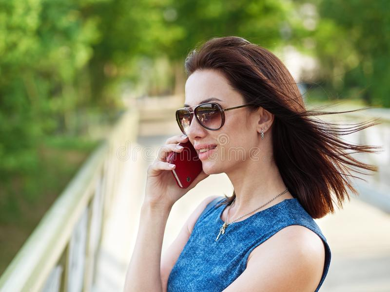 Atrakcyjna brunetki kobieta w okularach przeciwsłonecznych i niebiescy dżinsy sukni emocjonalną rozmowę telefoniczną na telefonie obrazy royalty free