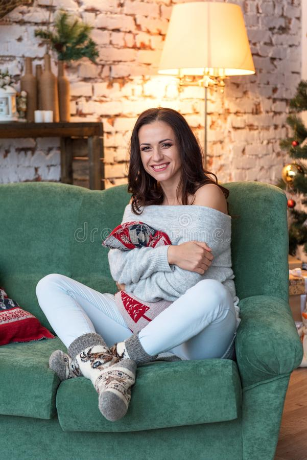 Atrakcyjna brunetki kobieta w rocznika pulowerze śmia się uśmiecha się szczęśliwie ściskający ochraniaczów w nowy rok dekorującym zdjęcia royalty free