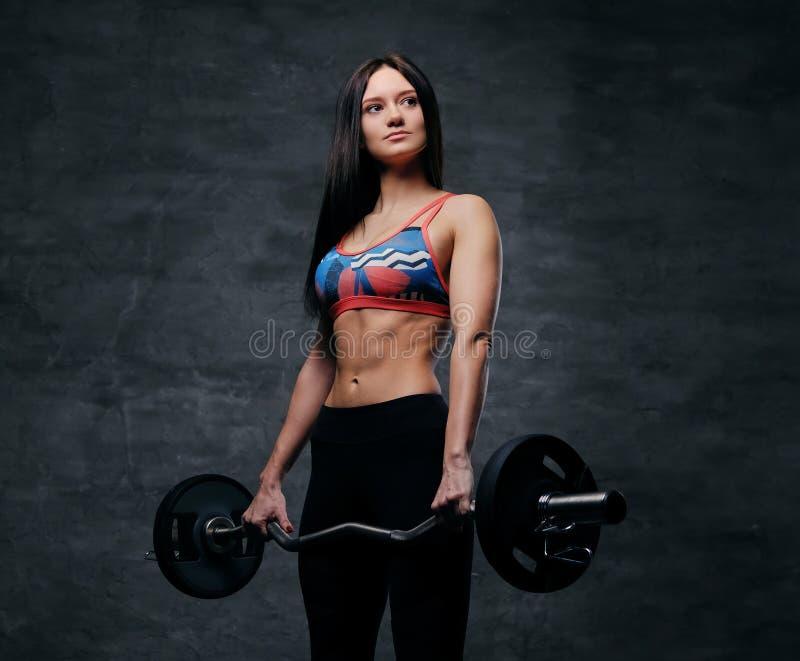 Atrakcyjna brunetki schudnięcia kobieta ubierał w sportswear trzyma b fotografia stock