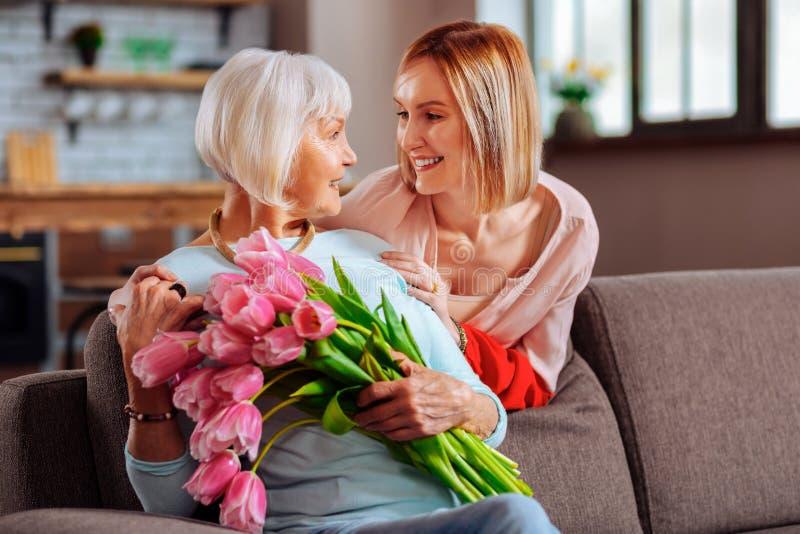 Atrakcyjna córka tenderly patrzeje starszy d uśmiechniętej matki zdjęcie royalty free