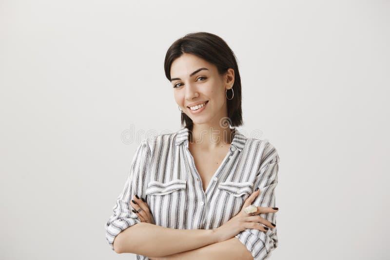 Atrakcyjna caucasian żeńska manicure'u producenta pozycja w ufnej pozie z krzyżować rękami, ono uśmiecha się szeroko z gwarantowa zdjęcie stock