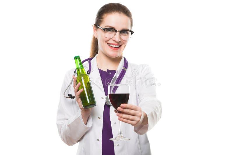 Atrakcyjna caucasian brunetki kobiety lekarki pozycja w biurze z butelką i szkłem wino w jej rękach na bielu zdjęcia stock