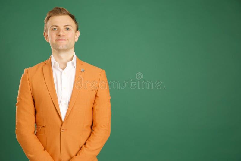 Atrakcyjna caucasian dorosła samiec jest ubranym pomarańczową kurtkę obrazy stock