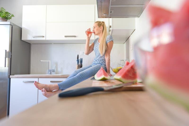 Atrakcyjna caucasian kobieta pije domowej roboty owocowego soku obsiadanie na kuchennym kontuarze Gospodyni domowa relaksuje w ku obrazy royalty free