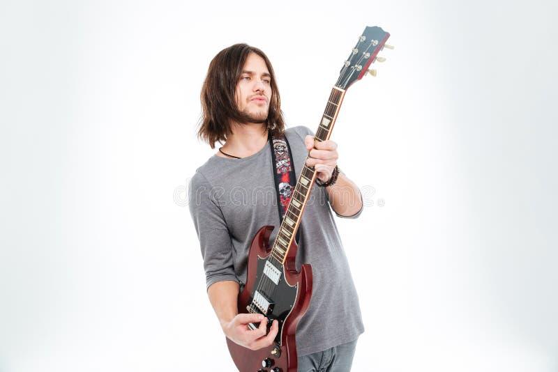 Atrakcyjna charyzmatyczna męska gitarzysta pozycja i bawić się gitara elektryczna zdjęcia royalty free