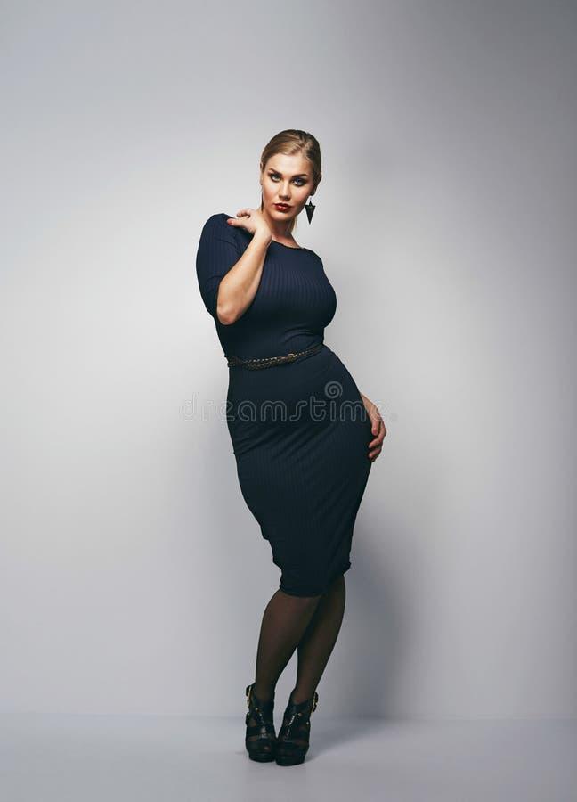 Atrakcyjna curvy kobieta w zmroku - błękit suknia obrazy royalty free