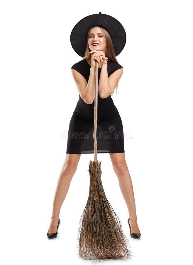 Atrakcyjna czarownicy dziewczyna z miotłą odizolowywającą na białym tle Halloweenowy kostiumu pojęcie obrazy royalty free