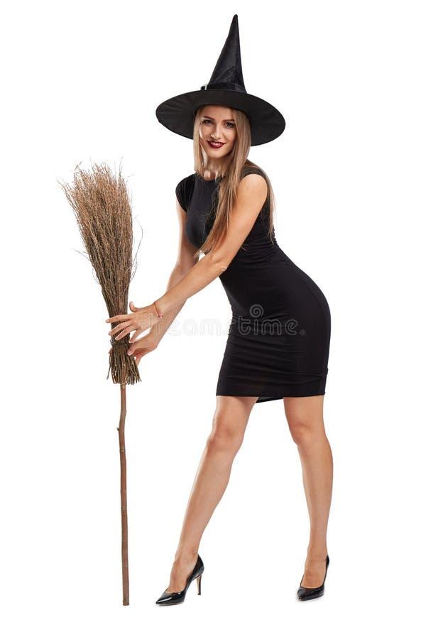 Atrakcyjna czarownicy dziewczyna z miotłą odizolowywającą na białym tle Halloweenowy kostiumu pojęcie obrazy stock