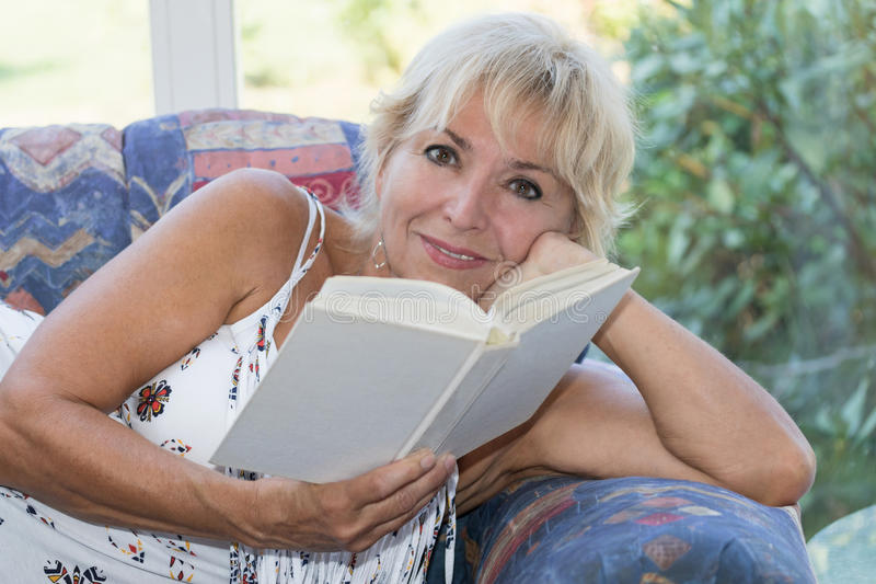 Atrakcyjna dojrzała blond kobieta czyta książkę zdjęcia royalty free