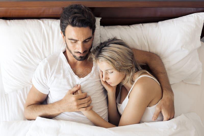 Atrakcyjna dosypianie para w sypialni zdjęcia stock