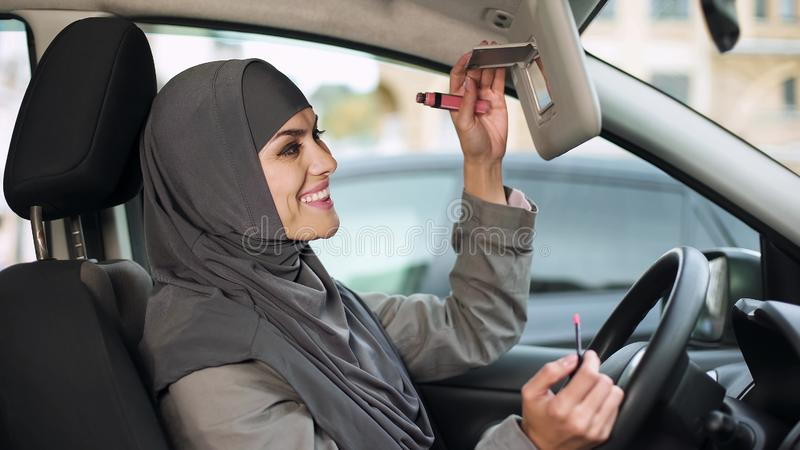 Atrakcyjna dufna Muzułmańska dama stosuje pomadki obsiadanie w samochodzie, kokietka obraz royalty free