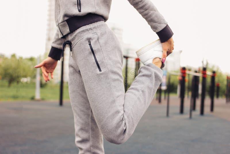 Atrakcyjna dysponowana młoda kobieta w popielatej sport odzieży robić grże w górę rozciągania przed trenować na ulicznym treningu fotografia royalty free