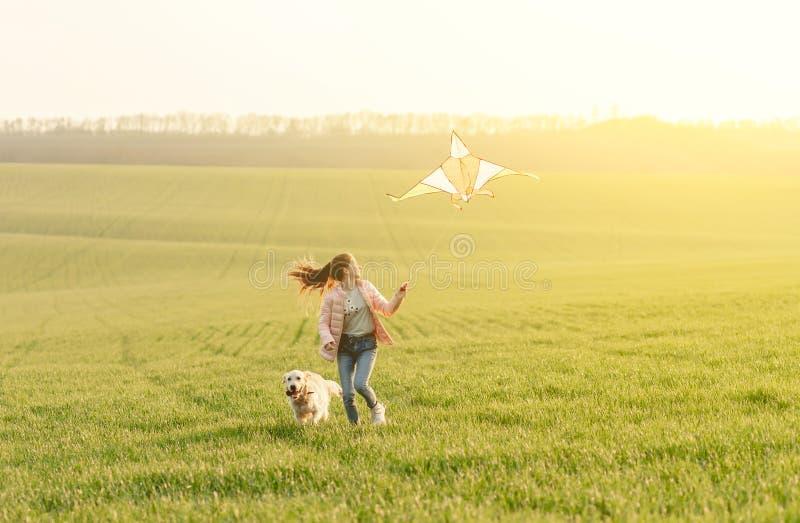 Atrakcyjna dziewczyna latająca latawcem na boisku zdjęcie stock