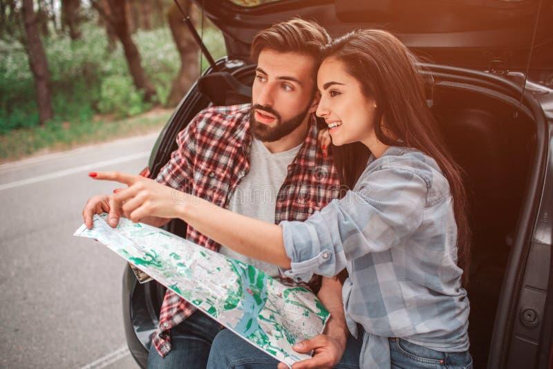 Atrakcyjna dziewczyna siedzi z jej chłopakiem w samochodowym ` s bagażniku i wskazywać bezpośrednim Jest uśmiechnięta Facet jest zdjęcia royalty free
