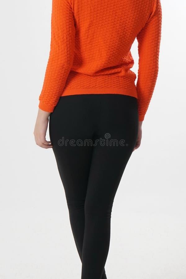Atrakcyjna dziewczyna w czarnych leggings i pomarańczowej bluzce w studiu fotografia royalty free