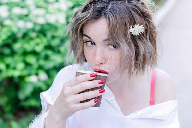 Atrakcyjna dziewczyna z czerwonymi wargami i manicure'u whith kwiatem w jej włosy siedzi w parku i pije kawę fotografia stock