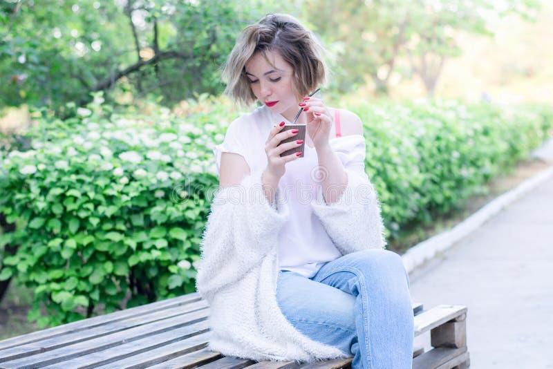 Atrakcyjna dziewczyna z czerwonymi wargami siedzi w parku z papierową filiżanką kawy obrazy royalty free