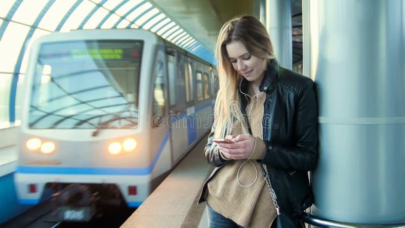 Atrakcyjna dziewczyna z gadżet blondynki długim włosy w skórzanej kurtce prostuje pozycję w metrze przeciw tłu obrazy stock