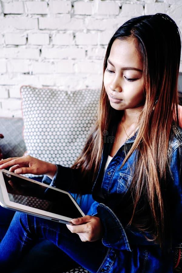 Atrakcyjna dziewczyna z pastylka komputerem w jej ręce obrazy stock