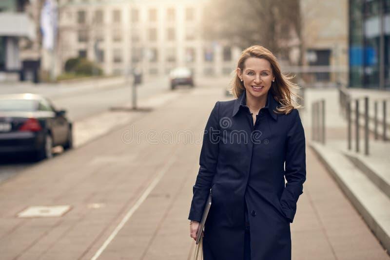 Atrakcyjna elegancka blond kobieta opuszcza jej miejsce pracy zdjęcie stock