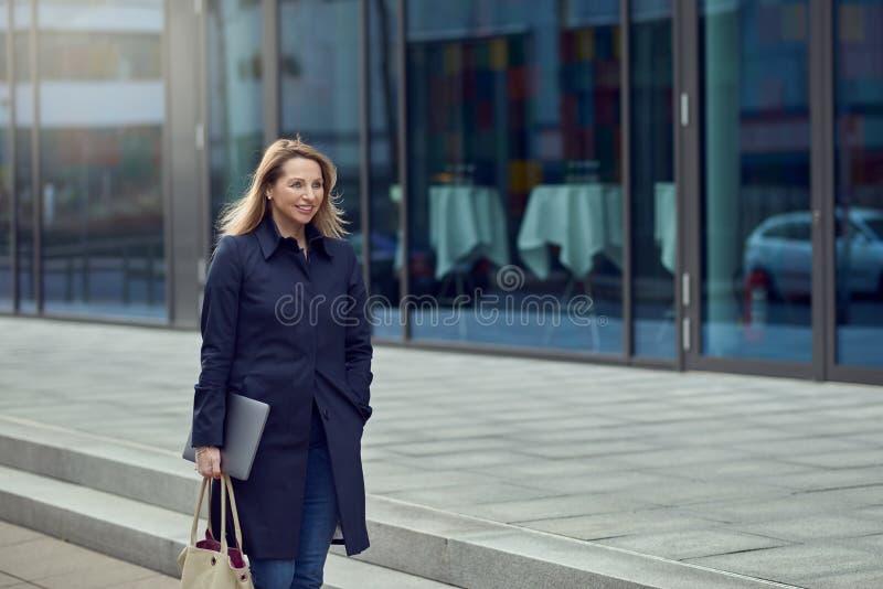Atrakcyjna elegancka blond kobieta opuszcza jej miejsce pracy zdjęcie royalty free