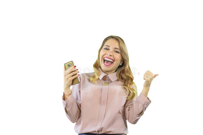 Atrakcyjna i radosna blondynki dziewczyna patrzeje w koszula jest stać z ukosa i patrzeć telefon w jej ręce obraz royalty free