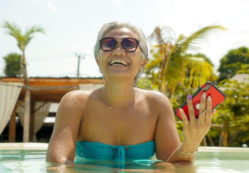 Atrakcyjna i szczęśliwa Azjatycka Indonezyjska w średnim wieku kobieta w bikini przy tropikalnym kurortu basenem używa ogólnospoł fotografia stock