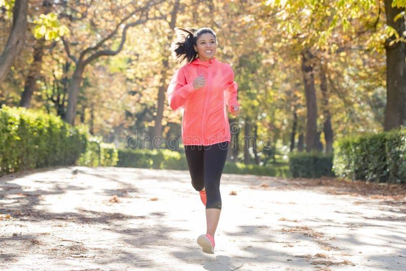 Atrakcyjna i szczęśliwa biegacz kobieta biega a w jesieni sportswear zdjęcia royalty free