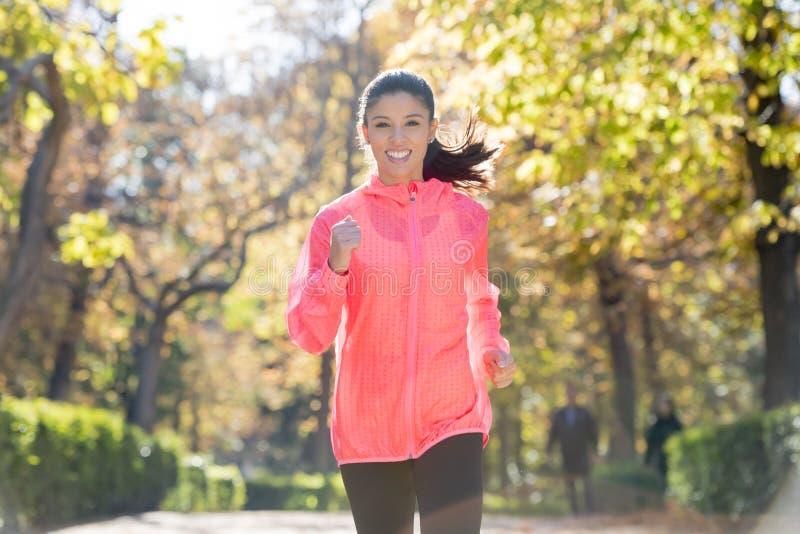 Atrakcyjna i szczęśliwa biegacz kobieta biega a w jesieni sportswear fotografia stock