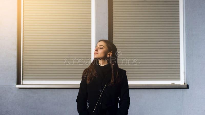 Atrakcyjna inspirowana młoda dama stoi outdoors na świetle słonecznym, cieszy się dobrego dzień fotografia stock