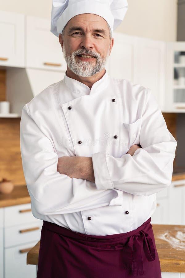 Atrakcyjna Kaukaska szef kuchni pozycja z r?kami krzy?owa? w restauracyjnej kuchni obraz royalty free