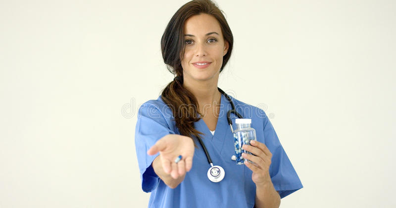 Atrakcyjna kobieta doktorska trzymający out pigułkę fotografia royalty free