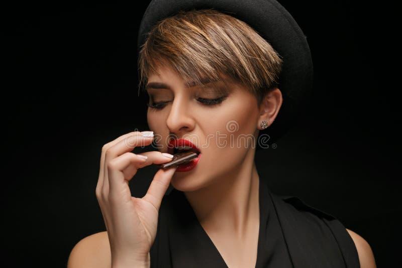 Atrakcyjna kobieta jest ubranym czarnego kapelusz i klasyczna koszulka jemy czekoladę w ciemnym tle obraz royalty free