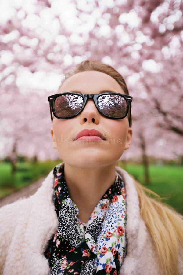 Atrakcyjna kobieta jest ubranym okulary przeciwsłonecznych przy wiosna parkiem zdjęcia stock