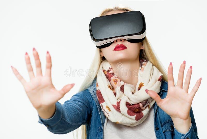 Atrakcyjna kobieta jest ubranym rzeczywistość wirtualna gogle VR słuchawki Rzeczywistości wirtualnej pojęcie na bielu fotografia stock