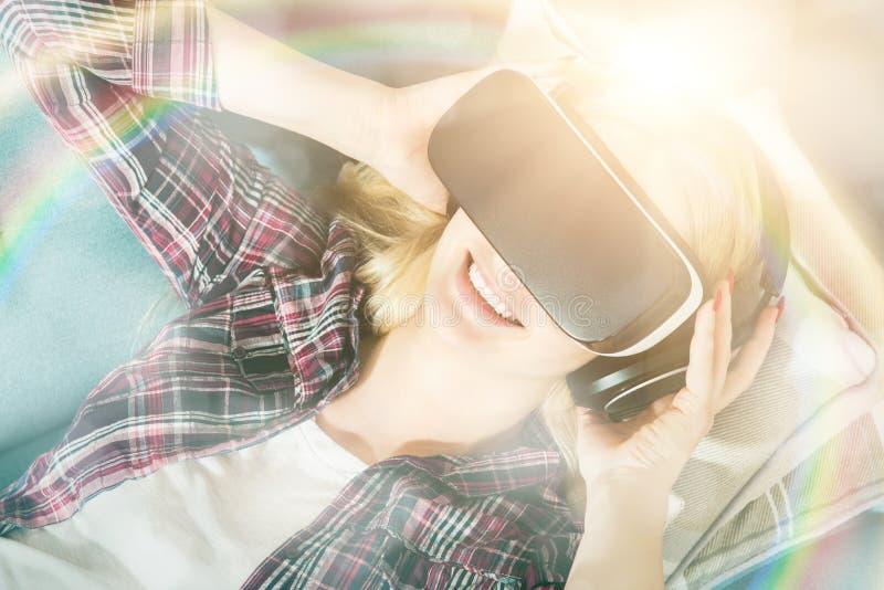 Atrakcyjna kobieta jest ubranym rzeczywistość wirtualna szkła kłama na leżance Rzeczywistości wirtualnej słuchawki Styl życia rze obrazy stock