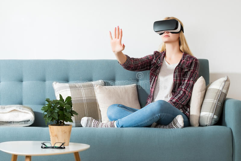 Atrakcyjna kobieta jest ubranym rzeczywistość wirtualna szkła siedzi na leżance Rzeczywistości wirtualnej słuchawki Styl życia rz obraz royalty free