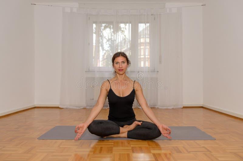 Atrakcyjna kobieta medytuje samotnie w pokoju obrazy royalty free