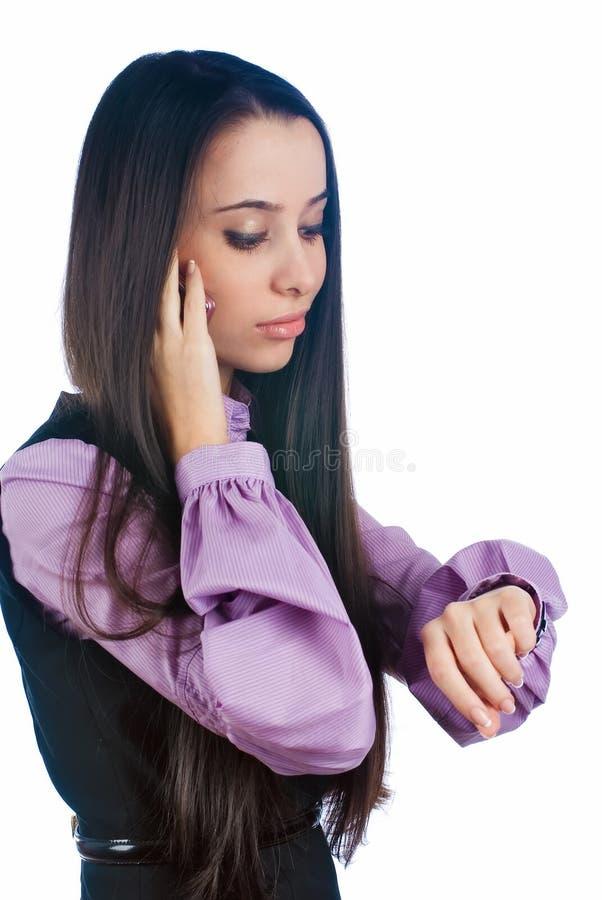 Atrakcyjna kobieta opowiada na telefonie i spojrzeniach na zegarku zdjęcie royalty free