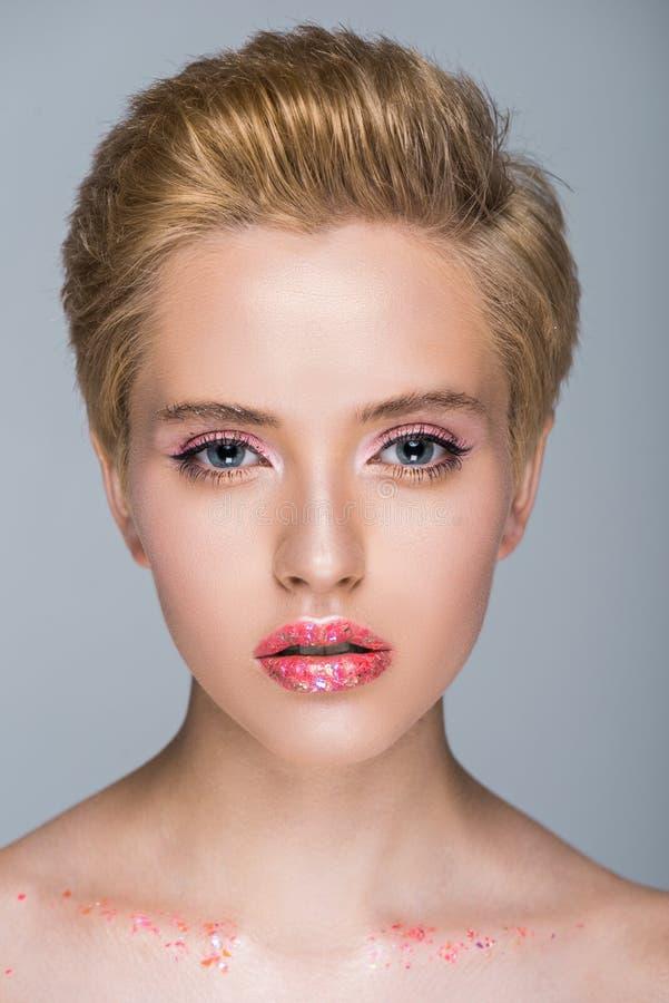 atrakcyjna kobieta patrzeje kamerę z błyskotliwym makeup i krótkim ostrzyżeniem zdjęcia stock