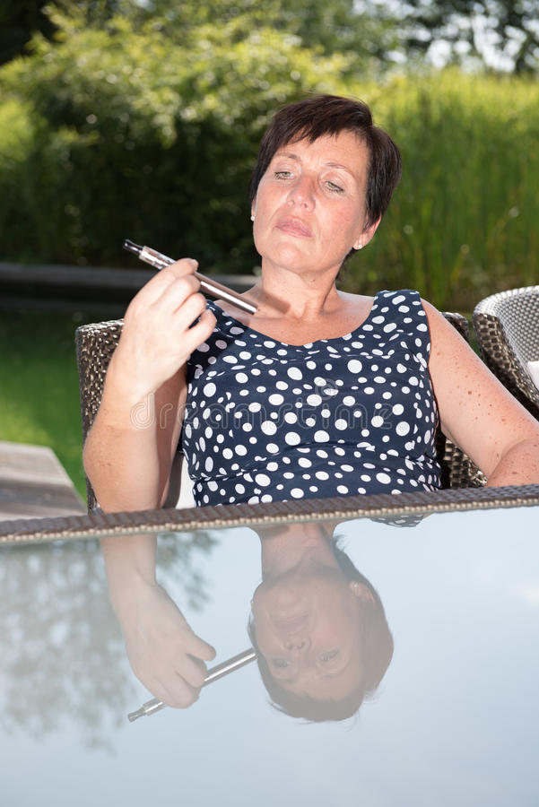 Download Atrakcyjna Kobieta Patrzeje Sceptyczną Na Papierosie W Ogródzie Obraz Stock - Obraz złożonej z palacz, błękitny: 57674413